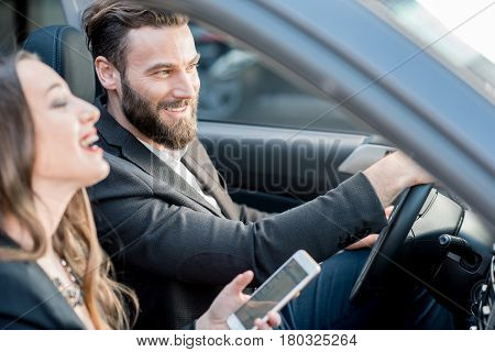 Business couple having funny conversation while driving a car in the city