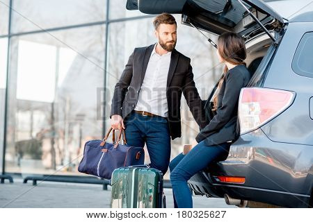 Business couple sitting in the car trunk with suitcase in the city. Business traveling by car concept