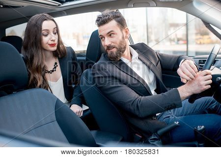 Businesswoman on the backseat with elegant man driving a car in the city. Worried about a delay to an important meeting