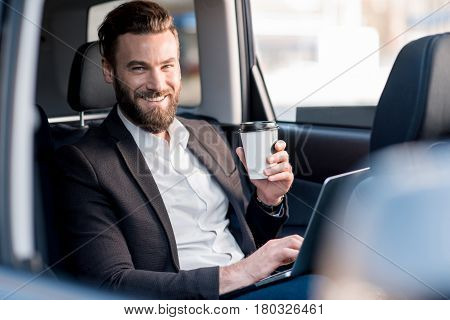 Handsome businessman sitting with coffee to go on the backseat of the car