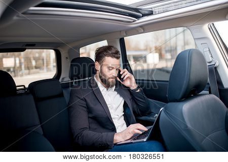Handsome businessman talking with phone sitting with laptop on the backseat of the car