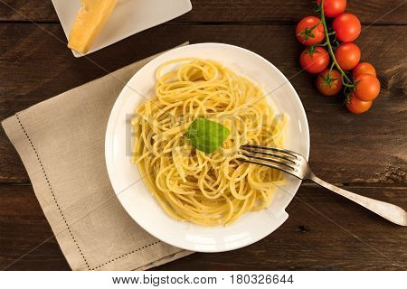 An overhead photo of a plate of spaghetti with a piece of cheese and cherry tomatoes, with a place for text