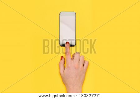 girl touch mobile or cell phone screen with hand has red manicure on yellow background. skincare internet surfing video conferencing communication copy space