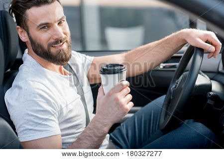 Portrait of a handsome man dressed cassual in white t-shirt driving a car with coffee to go