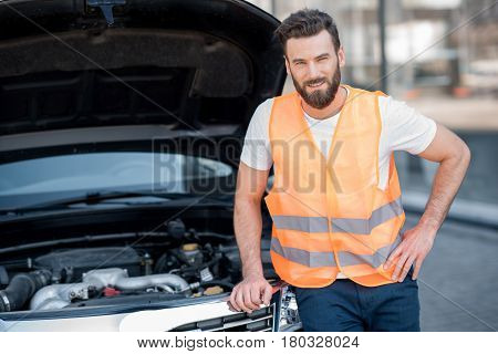Portrait of a handsome worker of an technical assistance service standing near the car