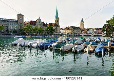 Zurich, Switzerland - September 2, 2016: St Peter Church Fraumunster Church and boats at Limmat River quay in the city center of Zurich Switzerland. People on the background