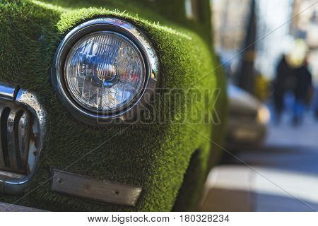 Front headlight of an old car in summer covered with artificial grass. Decorated on classical car.