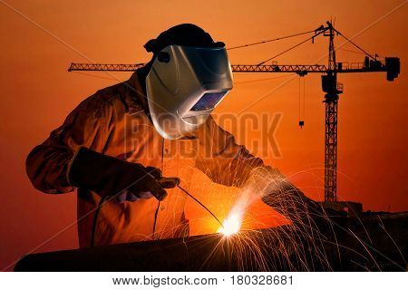 Welding Worker Welding Steel Structure With Construction Crane And Building At Construction Site On