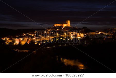 Mertola castle and the oldest part of town lighted at night over the River Guadiana down the slope. Alentejo Portugal.