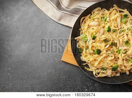 Frying pan with delicious chicken Alfredo on kitchen table