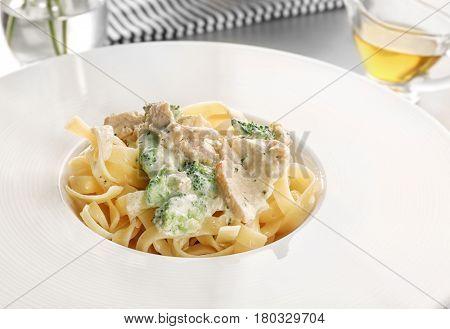 Delicious pasta alfredo with chicken on plate, closeup