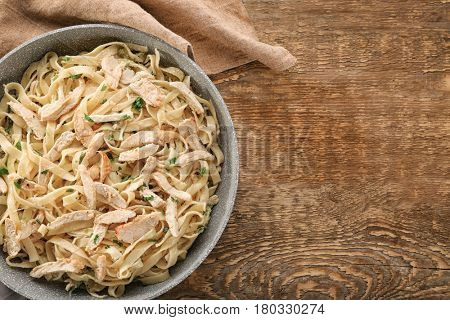 Frying pan with delicious chicken Alfredo on wooden table