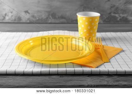 Yellow plastic disposable tableware on wooden table