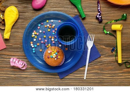 Plastic tableware with birthday cupcake on wooden table