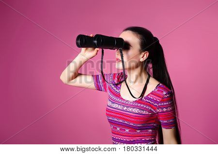 young woman with binoculars in hand on a pink background. Watching through Binoculars