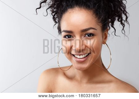 Closeup portrait of smiling woman looking at camera, wearing earrings