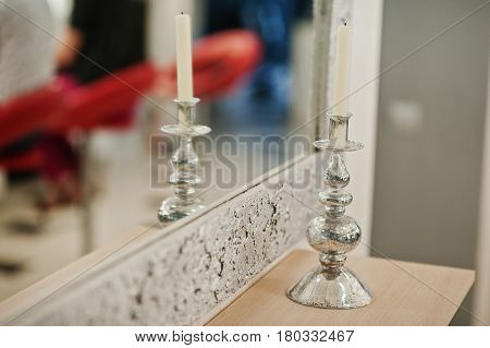 Candle On Silver Candlestick At Beauty Salon Against Mirror.