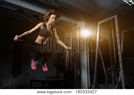 sporty girl blonde jumping over some boxes in a cross-training gym