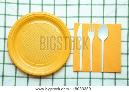 Yellow plastic disposable tableware on tablecloth