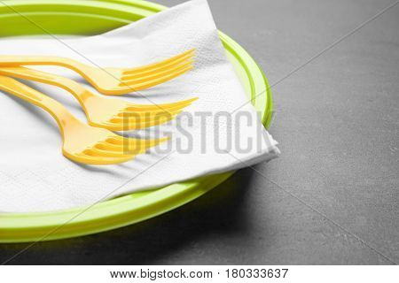 Green plastic disposable tableware on gray background
