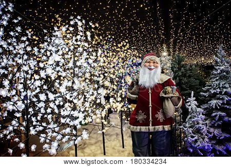 Santa Claus with decorative Christmas lights in a store