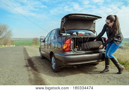 Woman Trys Get Wheel From The Trunk To Change It