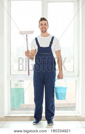 Young window cleaner with special supplies in office