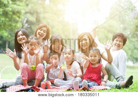Group of Asian multi generations family portrait, grandparent, parents and children, outdoor nature park in morning with sun flare.