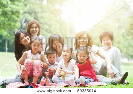 Beautiful Asian multi generations family portrait, grandparent, parents and children, outdoor nature park in morning with sun flare.