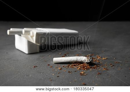 Damaged cigarette and pack on grey table