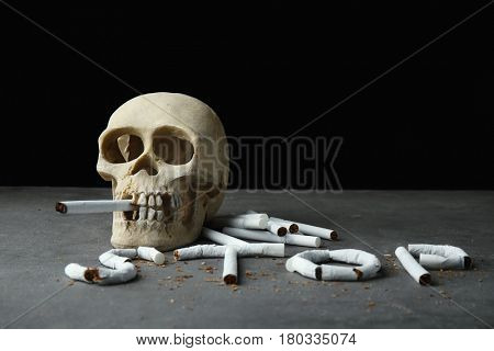 No smoking concept. Word STOP made of cigarettes and skull on grey background