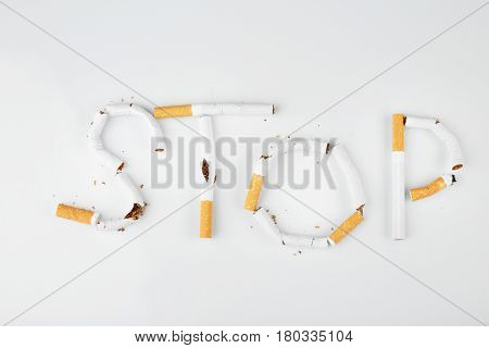 Word STOP made of cigarettes on white background