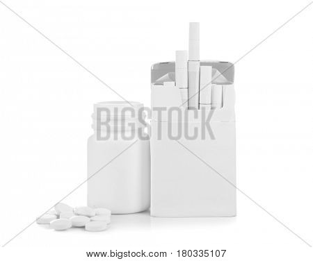 Pack of cigarettes and pills isolated on white