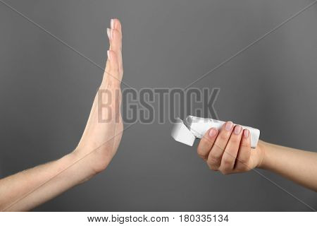 No smoking concept. Woman refusing of offered cigarette on grey background