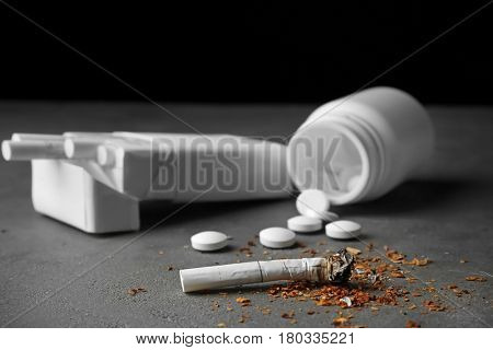 Damaged cigarette, pack and pills on grey table