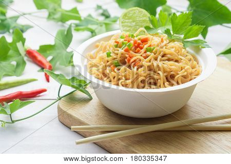 Instant noodles in paper bowl on white wooden background.