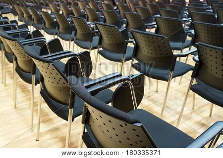 Conference chairs in business room rows of comfortable seats in empty corporate presentation meeting office detail selective focus
