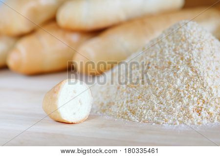 Pile of breadcrumbs and blurry bread rolls in the background