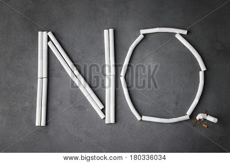Word NO made of cigarettes on grey background