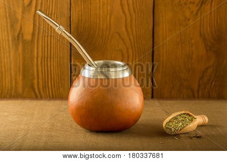 Calabash with yerba mate and a wooden spoon against the background of a tree