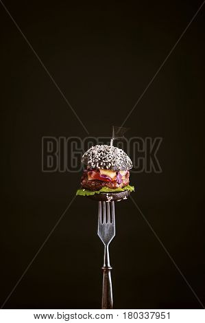 Black mini burger on the fork in rustic style