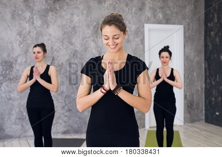 Young sportive trio group of girls are practicing yoga exercises in the studio.
