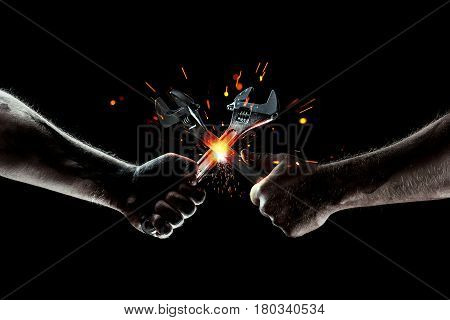 The battle of mechanics. Two wrenches cut sparks. Strong man's hands with wrenches