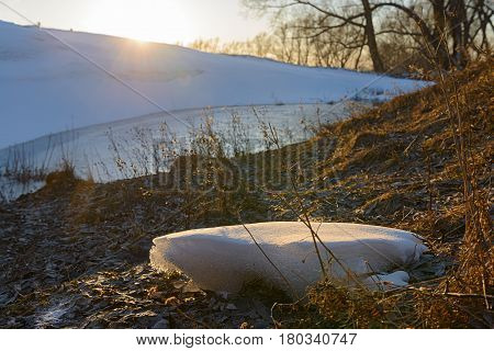 Spring landscape with snow snowdrifts and a pond