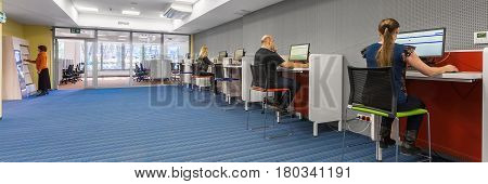 Panorama of modern college interior with functional workstations with new computers
