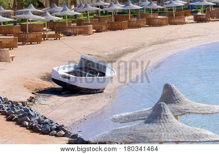 Idyllic tropical beach with white motor boat on golden sand umbrellas sun beds at beautiful blue sea shore coast on bright sunny day on natural background. Summer vacation in paradise
