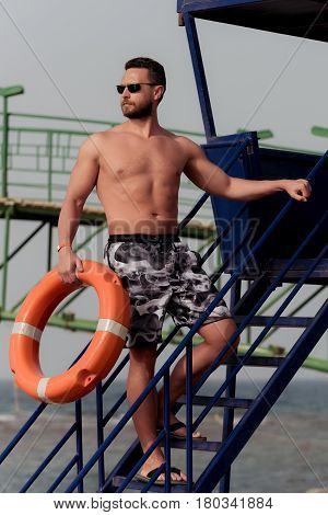 muscular man bearded lifeguard with muscle torso with orange ring buoy for life saving on duty on tower overlooking sea ocean beach sunny summer day on blue sky background. Safety rescue vacation