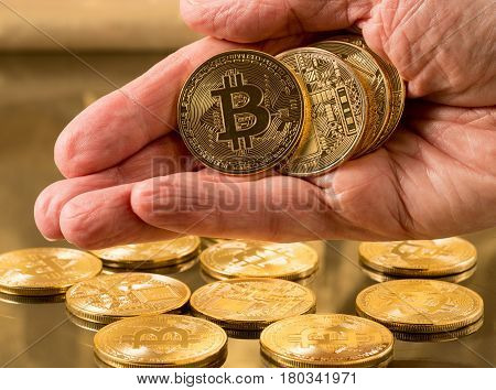 Stack of bit coins or bitcoin held in man's hand on gold background to illustrate blockchain and cyber currency