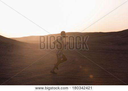 healthy lifestyle and success. man runner or fit male athlete running in desert sand dune at mountain in sun ray at sunset sunrise outdoor on white sky background. sprinting sport and marathon workout