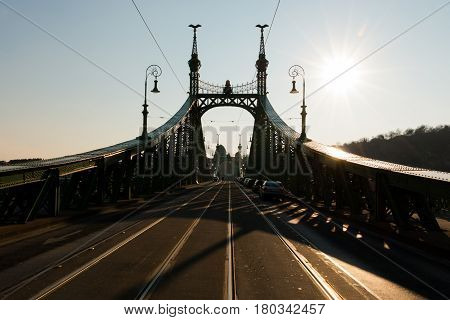 Budapest, Hungary - March 08, 2017: Street view of carriageway and tram rails on Liberty Bridge on sunset, connects Buda and Pest across the river Danube